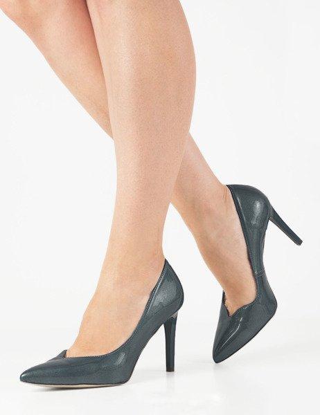 Kobiece nogi w szpilkach i lakierowana torebka
